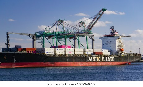 San Pedro, California USA - February 5, 2019: Loaded container ship NYK Maria in the of Port of Los Angeles passing docks and gantry cranes.