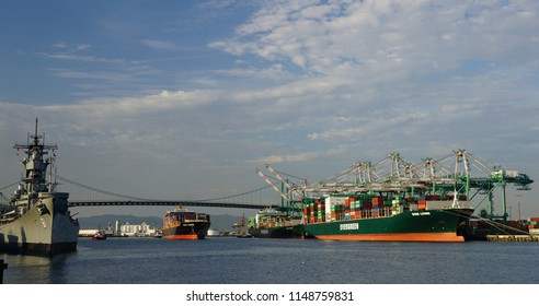 San Pedro, California USA - July 31, 2018: Port of Los Angeles main channel with Battleship Iowa, container ship, Vincent Thomas bridge and more ships at berths being loaded by gantry cranes