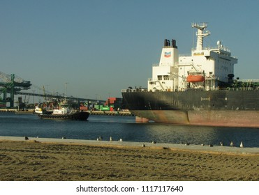 San Pedro, California USA - June 18 2018: Large tugboat guides an oceangoing petroleum tanker ship along the main channel of the Port of Los Angeles harbor.