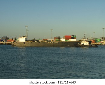 San Pedro, California USA - June 18 2018: A heavy duty tugboat guides an industrial transportation barge through the main channel of the Port of Los Angeles harbor.