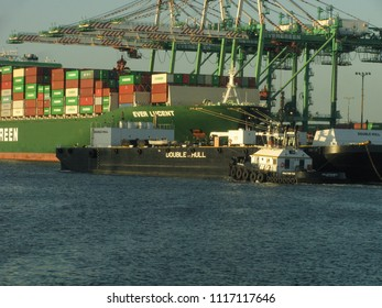 San Pedro, California USA - June 18 2018: An oceangoing tugboat guides an industrial transportation barge through the Port of Los Angeles harbor past a container ship and gantry cranes.