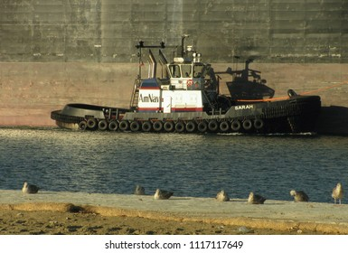 San Pedro, California USA - June 18 2018: Large tugboat guides an oceangoing oil tanker ship in the harbor main channel of the Port of Los Angeles