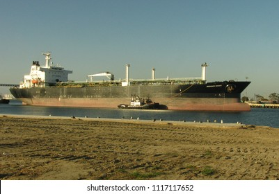 San Pedro, California USA - June 18 2018: Oceangoing petroleum tanker ship 183 meters long guided by a tugboat in the main channel of the Port of Los Angeles harbor