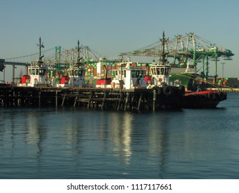 San Pedro, California USA - June 18 2018: Four heavy duty harbor tugboats moored in the main channel of the Port of Los Angeles with container ships and cranes background.