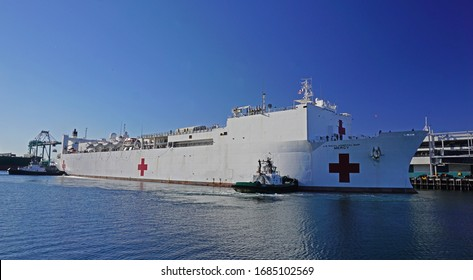 San Pedro, California USA - March 27, 2020: US Navy Hospital ship Mercy docks at the Port of Los Angeles harbor, assisted by tugboats, to provide medial assistance during Covid-19 coronavirus pandemic