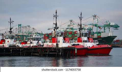 San Pedro, California USA - September 4, 2018: Tugboats docked in the Port of Los Angeles harbor, container ships berthed for loading by tall gantry cranes. Vincent Thomas suspension bridge in rear
