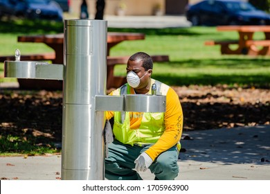 San Pedro, CA/USA - April 14, 2020: Parks and Recreation worker cleans water fountain at Point Fermin Park during Covid-19 stay at home order.
