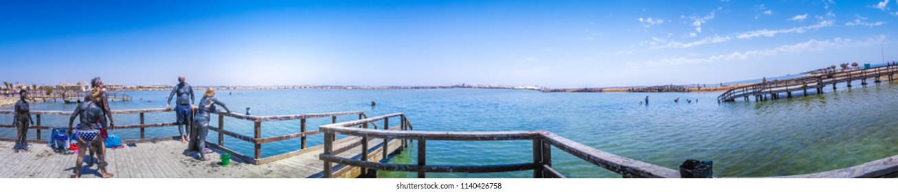 San Pedro del Pinatar, Murcia, Spain; 06 10 2015: A panoramic view of a group of tourists enjoying the therapeutics, free, open air public black mud baths in a sunny day with clear blue sky and water.