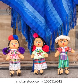 San Pedro / Guatemala - April 27, 2016: Traditional Mayan dolls from Guatemala in original clothing in San Pedro, Lake Atitlan, Guatemala. Traditional  Guatemalan weaves in the background. (1x1)