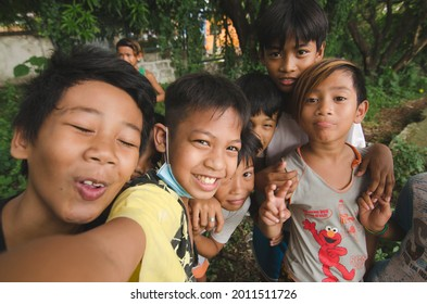 San Pedro, Laguna - July 2021: A few impoverished but happy and friendly Filipino children gather together to take a fun selfie.