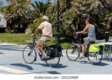 SAN PEDRO, SPAIN - MAY 2018: Summer cycling. An elderly couple cycling in the park.