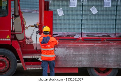 San Pellegrino Italy February 14th 2019: Truck driver secures the loading of bottles of mineral water by binding it with ropes before starting the transport