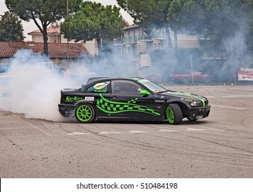 """SAN PIETRO IN VINCOLI, RA, ITALY - OCTOBER 23: crew on a drift racing car BMW in action drifting with smoking tires  in """"Telethon Motor Show"""" on October 23, 2016 in San Pietro in Vincoli, RA, Italy"""
