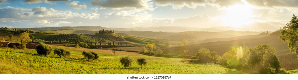 San Quirico d'Orcia, Italy - October 30th 2018: Panoramic autumn sunrise over Belvedere in Tuscany with wavy landscape, cypresses burning sun and cloudy sky