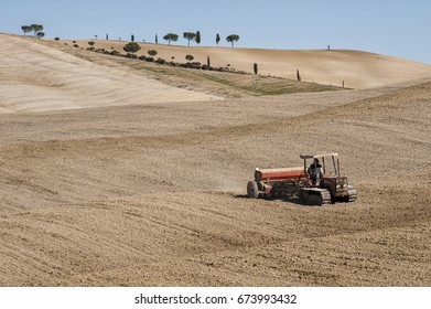 SAN QUIRICO D'ORCIA, TUSCANY / ITALY - OCTOBER 31, 2016: Undefined farmer on a tractor in the beautiful tuscan landscape near San Quirico d'Orcia with rolling hills in autumn.