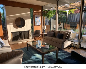 San Rafael, California/USA - November 2, 2019: the golden hour sunshine hits the living room just right,  in a vintage Eichler with modern style furniture and wide windows