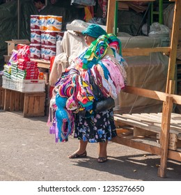 San Salvador / El Salvador - April 23, 2016: Unidentified female street vendor carrying underwear in the downtown San Salvador, El Salvador. The city has been home to an informal market for years.