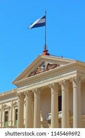 San Salvador / El Salvador; December 22nd, 2017: The facade of the Palacio Nacional in the heart of the the city with the Salvadoran national flag waving above it.