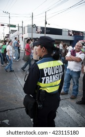 San Salvador / El Salvador - March, 19, 2011: A policewoman overlooks at the crowd in a busy intersection.