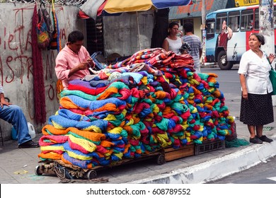 SAN SALVADOR, EL SALVADOR-MAY 8, 2007:  A side-walk street vendor waits for a customer to sell one of his colorful blankets or hammocks to passersby on a busy street in the nation's capital.