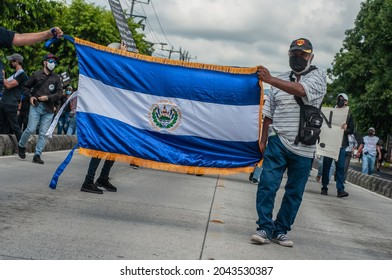 San Salvador, El Salvador - September 15th, 2021: Protesters hold national flags and march against the politics of current president Nayib Bukele.
