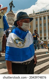 San Salvador, El Salvador - September 15th, 2021: A civil war veteran protests against the politics of current president Nayib Bukele by wrapping the national flag around him.