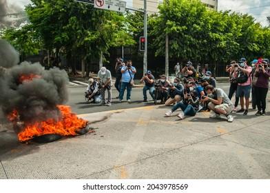 San Salvador, El Salvador - September 15th, 2021: Journalists capture images of tires set on fire by potesters.