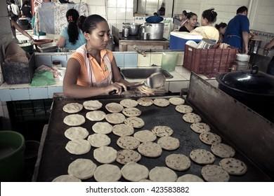 San Salvador / El Salvador - September 9 2009: A lady prepares a handful of salvadoran style tortillas for lunch.