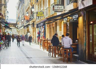SAN SEBASTIAN, SPAIN - APRIL 6, 2019: People enjoying wine and pinchos in various bars and cafes of San Sebastian (Donostia), Spain