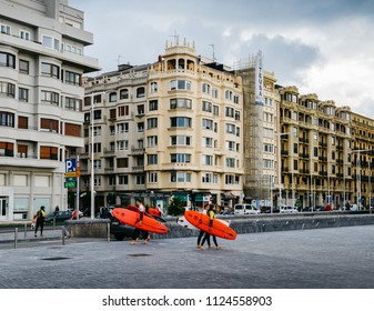 San Sebastian, Spain - June 13, 2018: Sufers heading to the beach with traditional art-nouveau architecture in background