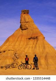SAN SEBASTIAN, SPAIN - March 10, 2019: Cyclists next to the tourist attraction Castildeterra in the desert of the Bardenas, Navarra