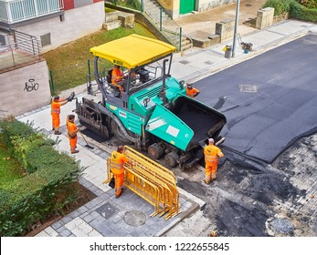San Sebastian, Spain - October 10, 2018. Laborers leveling fresh asphalt with a modern asphalting paver machine during the works for the pavement rehab of a road.