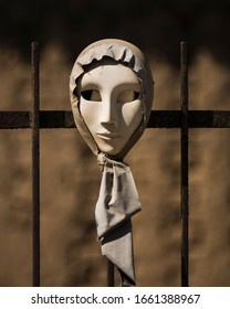 SAN SPERATE, SARDINIA, ITALY - SEPTEMBER 30th 2019 : White female mask wrapped in a headscarf hunging on an iron grille for an exhibition in the street.