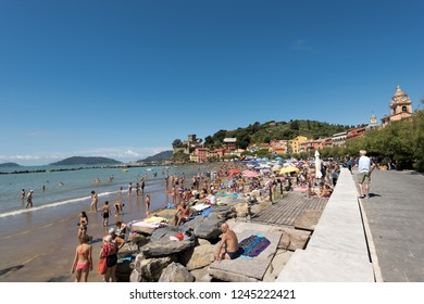 SAN TERENZO, LA SPEZIA, ITALY - JULY 10, 2014: San Terenzo (St. Terenzo) beach, crowded with bathers in a sunny day. Lerici, in the Gulf of La Spezia, Liguria Italy