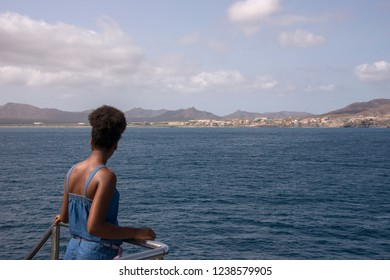 San Vicente, Cape Verde - September 29, 2015: Rear image of a young girl contemplating the city of Mindelo from the rail of a ferry, approaching the port