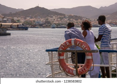 San Vicente, Cape Verde - September 29, 2015: Backlit image of a group of young people contemplating the city of Mindelo from the railing of a ferry approaching the port