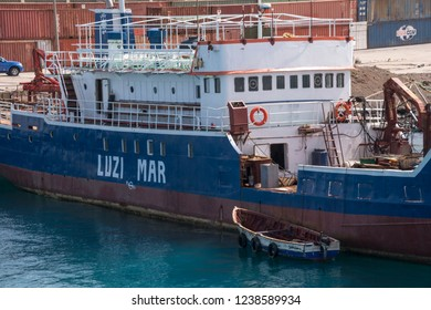 San Vicente, Cape Verde - September 29, 2015: Image with a small boat moored next to an old cargo ship, on the docks of the commercial port of the city of Mindelo, capital of the island