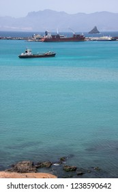 San Vicente, Cape Verde - September 29, 2015: Old cargo ships anchored in the waters of the bay of the city of Mindelo, capital of the island, with the islet of the lighthouse on the horizon