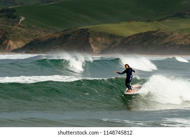 San Vicente de la Barquera, Cantabria/Spain- 01 03 2015:Surfer riding a wave with a longboard on the north of Spain, Cantabria