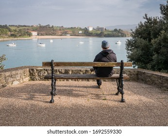 San Vicente de la Barquera, Cantabria, Spain - February 28, 2020: Solitary traveller on a bench and view over the bay and estuary