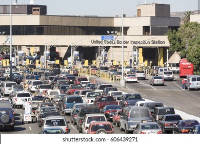 San Ysidro, California, USA - 15 November 2006: Vehicles lined up for US immigration and customs processing at the border entry point from Tijuana. Several officers and pedestrians are visible.
