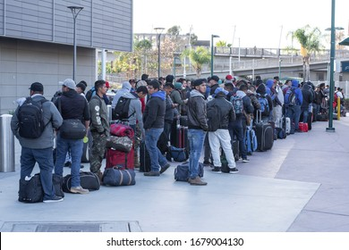San Ysidro, California / USA - March 20, 2020: Migrant workers from Mexico wait for transportation to seasonal work destinations before potential border closing due to the Coronavirus pandemic.