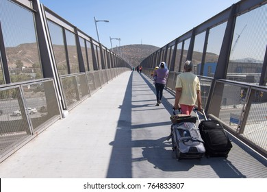 SAN YSIDRO, CALIFORNIA, USA - OCTOBER 5, 2017: Travelers cross the new pedestrian bridge over the interstate 5 freeway to the San Ysidro border crossing into Mexico