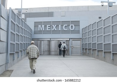 SAN YSIDRO, UNITED STATES - NOVEMBER 27, 2013: Pedestrians walk through the revolving metal gate from the U.S. to Mexico at the new international border crossing in San Ysidro on November 27, 2013