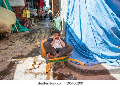 SANA'A, YEMEN - JAN 11, 2014: Unidentified Yemeni  boy sits in a carriage in Sana'a. People of Yemen suffer of poverty due to the unstable political and poor economical situation
