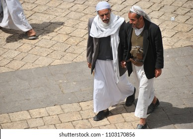 Sanaa, Yemen - March 6, 2010: Two unidentified hand in hand walking men chat on a street in the old city Sanaa