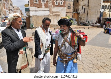 Sanaa, Yemen - March 6, 2010: Street scene on the street in old city. Armed antique rifle senior man talking with people. Inhabited for more than 2.500 years Sanaa is now destroyed by the civil war
