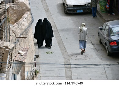 Sanaa, Yemen - March 6, 2010: Two women in a black burkas and other pedestrians walking down a street in old city of Sanaa