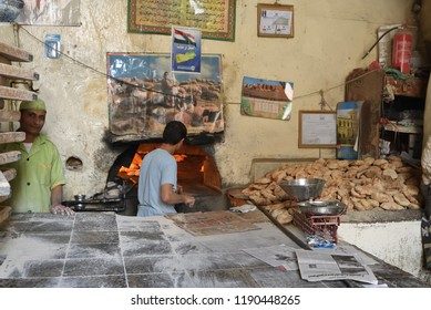 Sanaa, Yemen - March 6, 2010: Unknown men cook breads in the street bakery in Sanaa. Inhabited for more than 2500 years at an altitude of 2.200 m the Old City of Sanaa is a UNESCO World Heritage City