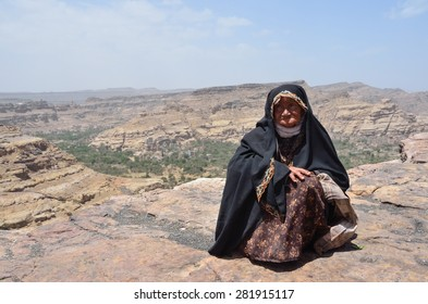 Sana'a, Yemen, March,18,2014. Yemeni scene: elderly poor woman sitting on the ground in the mountains